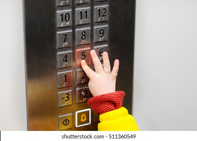 Hand of little child pressing button of five floor in elevator