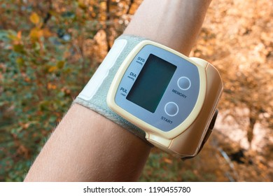 hand with little electric tonometer for pulse and blood pressure on the autumn backgorund. Medicine, age, healthcare and people concept with tonometer on the blurred background