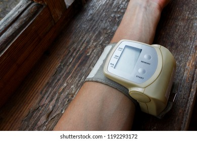 hand with little electric tonometer for pulse and blood pressure measurement on grunge old wooden background. Medicine, age, healthcare and people concept with tonometer on the green background