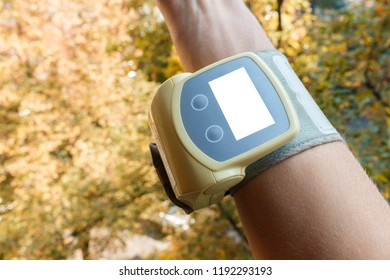 hand with little electric tonometer white mocap for pulse and blood pressure numbers on the autumn trees backgorund. Medicine, age, healthcare and people concept with tonometer on the arm