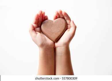 hand of a little girl with a heart-shaped chocolate in hand on white background.
