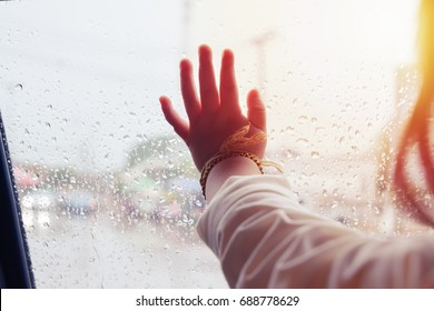 Hand of Little girl looking out of the window with light flare and rain drop on the car door glass, on raining day .