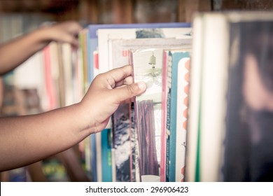 hand of little girl selecting a book from book shelf in vintage color tone
