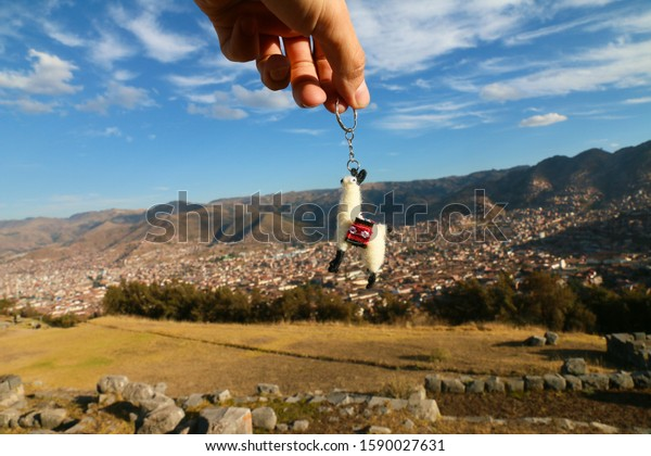hand with a llama keychain against the background of the city from the heights of the mountains watches the city, product advertisement