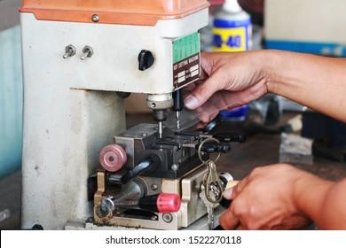 hand of  Locksmith copying car key with key copy machine.Close view of key copying machine . Duplicate machine make new key
