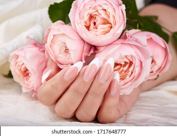 Hand with long artificial french manicured nails holding pink rose flowers