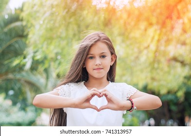 Hand love. Pretty little girl showing a heart symbol in the park on warm and sunny summer day. Sunlight effect.  Happy childhood concept. Love symbol. Girl making heart shape with hands.