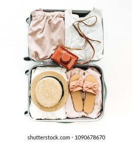 Hand luggage with stylish female clothes on white background. Flat lay, top view. Summer travel fashion concept.