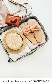Hand luggage with stylish female straw, slippers and retro camera on white background. Flat lay, top view. Summer fashion clothes and travel concept.
