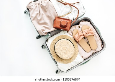 Hand luggage with stylish femininine clothes and retro camera on white background. Flat lay, top view. Summer fashion clothes concept.