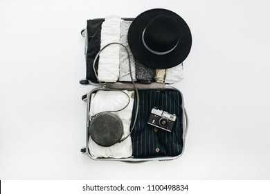 Hand luggage with stylish woman's clothes on white background. Flat lay, top view. Summer travel fashion concept.