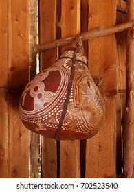 Hand made African water container hanging from a pole in a wooden structure