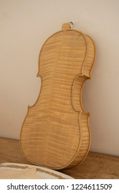 Hand made body of Cello, or violoncello, leaning against wall at musical craftmans workshop before completion