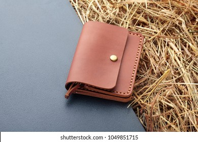 Hand made brown leather man wallet . Multi colored. Leather craft.On dark background.Top view
