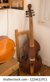 Hand made Cello, or violoncello, at musical craftmans workshop leaning against the wall, with wood shaving on floor