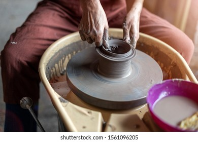 Hand made ceramics are formed by a mature woman on a potters wheel