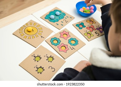 Hand made children home activity from cardboard and pom poms. Early education, Montessori methodology. Implement to develop fine motoric skills, logical thinking learn counting.