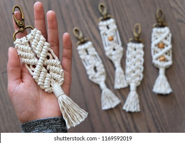 Hand made cotton macrame key chain close up with four blurred in the background that have different styles and some have beads. The background is a beautiful wooden floor.