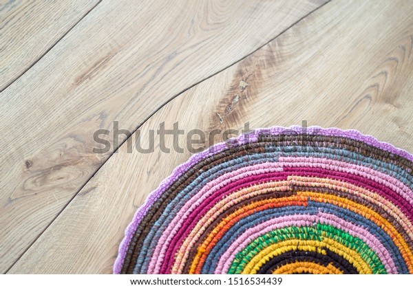 Hand made crocheted bright round rug on natural solid wood floor