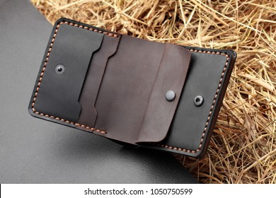 Hand made dark brown leather man wallet . Multi colored. Leather craft.On dark background.Top view