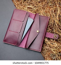 Hand made dark magenta leather man wallet .Man clutch with telephone. Multi colored. Leather craft.On dark background.Top view.