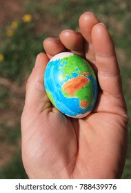 hand made Easter egg with a design of the earth held in a man's hand