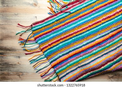 Hand made knitted multicolored plaid on a wooden background. Top view.