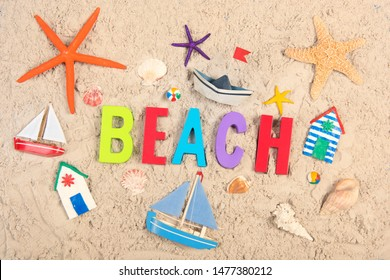 Hand made Miniature beach huts boats and shells in sand