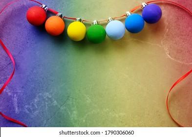 Balles de décoration de Noël peintes à la main dans les couleurs de l'arc-en-ciel sur table en pierre