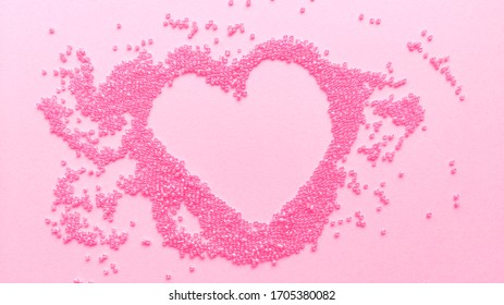 Hand made pink heart of beads on pastel texture background. Flat lay with copy space. Stock photo.