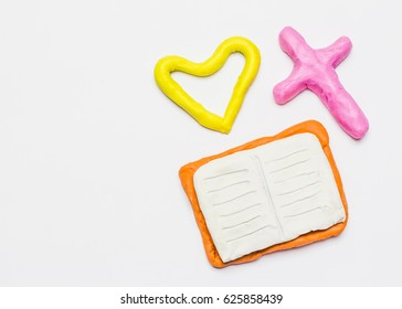 Hand made Plasticine figure of  bible, cross and heart by on white background with copy space