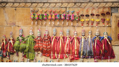 hand made puppets attached to string in Rajasthan India dolls. Women face with traditional Indian makeup wearing saree / sari