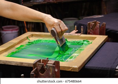 hand made screen printing tee shirt in love design. put block screen print of green color on tee shirt put green ink on block screen the press green ink by rubber handle