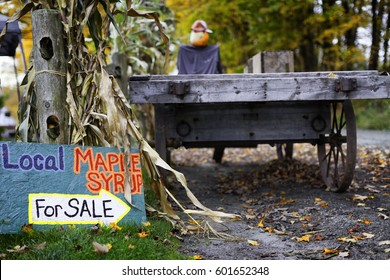 Hand made sign next to a Vermont country road stand selling local maple syrup. Vintage wood wagon. Autumn leaves, picturesque scenic setting
