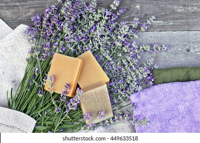 Hand made soap with lavender, towels , candle on wooden table