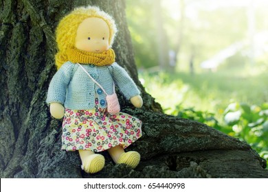 Hand made textile waldorf doll on wooden tree background
