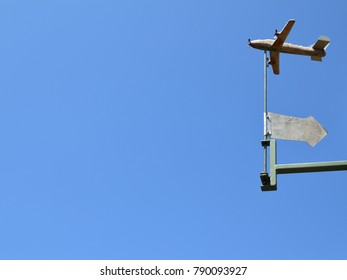 Hand made weather vane with an arrow, small plane and clear blue sky