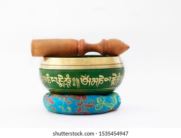 """Hand made yellow and green Singing Bowl with written Tibetan language means mantra""""om mani padme om"""" , used for meditation and yoga, with stick and multi color cushion as a base with  isolated white b"""