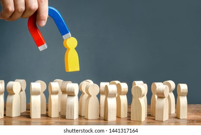 A hand with a magnet pulls goldem yellow human figure out of the big crowd of people. Search for talented workers Labor migration, the demand for good specialists. Recruiting new workers, headhunters.