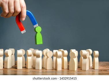 A hand with a magnet pulls green human figure out of the big crowd of people. Recruiting new workers, headhunters. Search for talented workers Labor migration, the demand for good specialists.