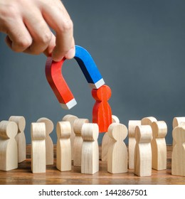 The hand with a magnet pulls out a red figure of a man from the crowd. Increase team efficiency, productivity. leader manages the business and forms a team. toxic, incompetent worker.