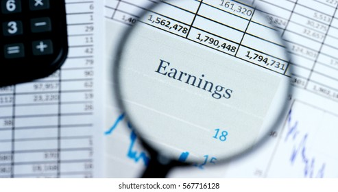 """A hand with a magnifying glass passes over a financial newspaper and financial bag with a business plan. The lens magnifies the word """"Earnings"""". Concept: economy, finance, crisis, business plan,"""