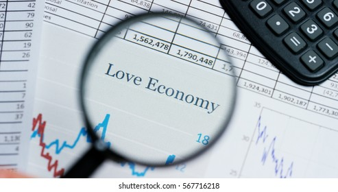 """A hand with a magnifying glass passes over a financial newspaper and financial bag with a business plan. The lens magnifies the word """"Love Economy"""". Concept: economy, finance, crisis, business plan,"""