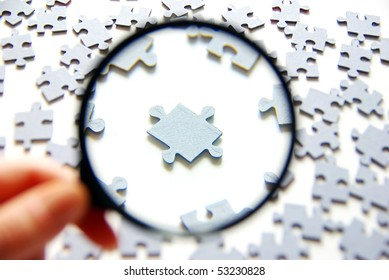 Hand with magnifying glass and puzzle