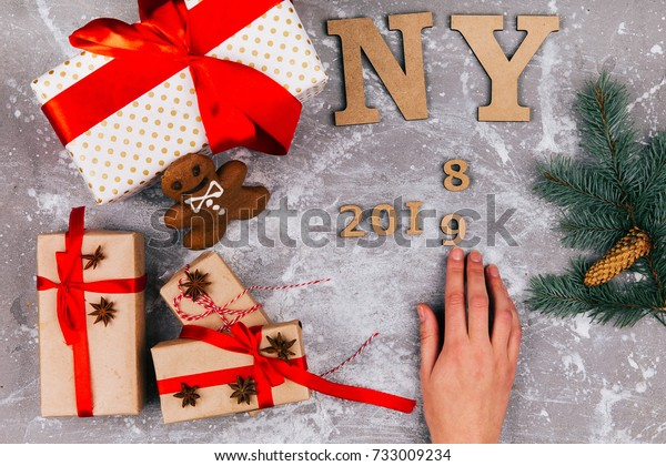 Hand makes number 2018 to 2019 on grey floor covered with Christmas present boxes