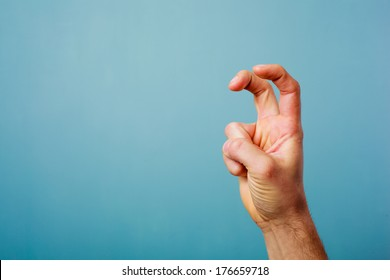 Hand making bunny ears with two fingers against blue background