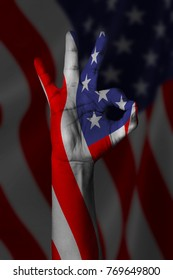 Hand making Ok sign, American flag painted as symbol of best quality, positivity and success - isolated on flag background