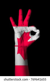 Hand making Ok sign, Canada flag painted as symbol of best quality, positivity and success - isolated on black background