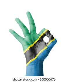 Hand making Ok sign, Tanzania flag painted as symbol of best quality, positivity and success - isolated on white background