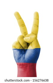 Hand making the V sign, Colombia flag painted as symbol of victory, win, success - isolated on white background